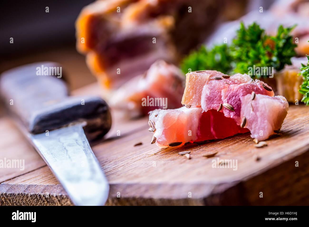 Roher geräucherter Speckscheiben auf Holzbrett mit Kümmel und Kräuter. Stockbild