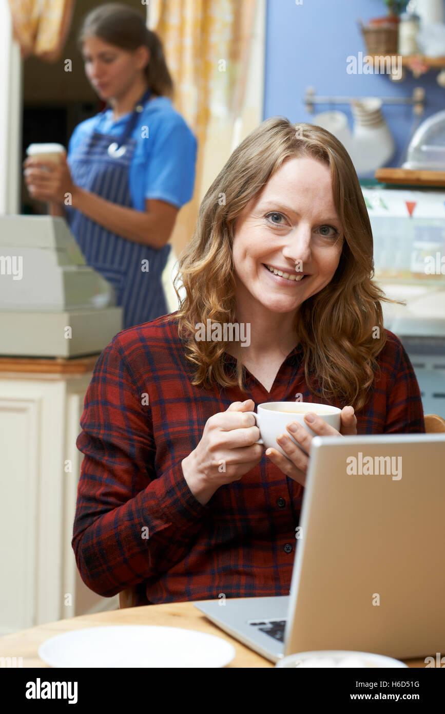 Frau In Coffee-Shop mit Laptop-Computer Stockbild
