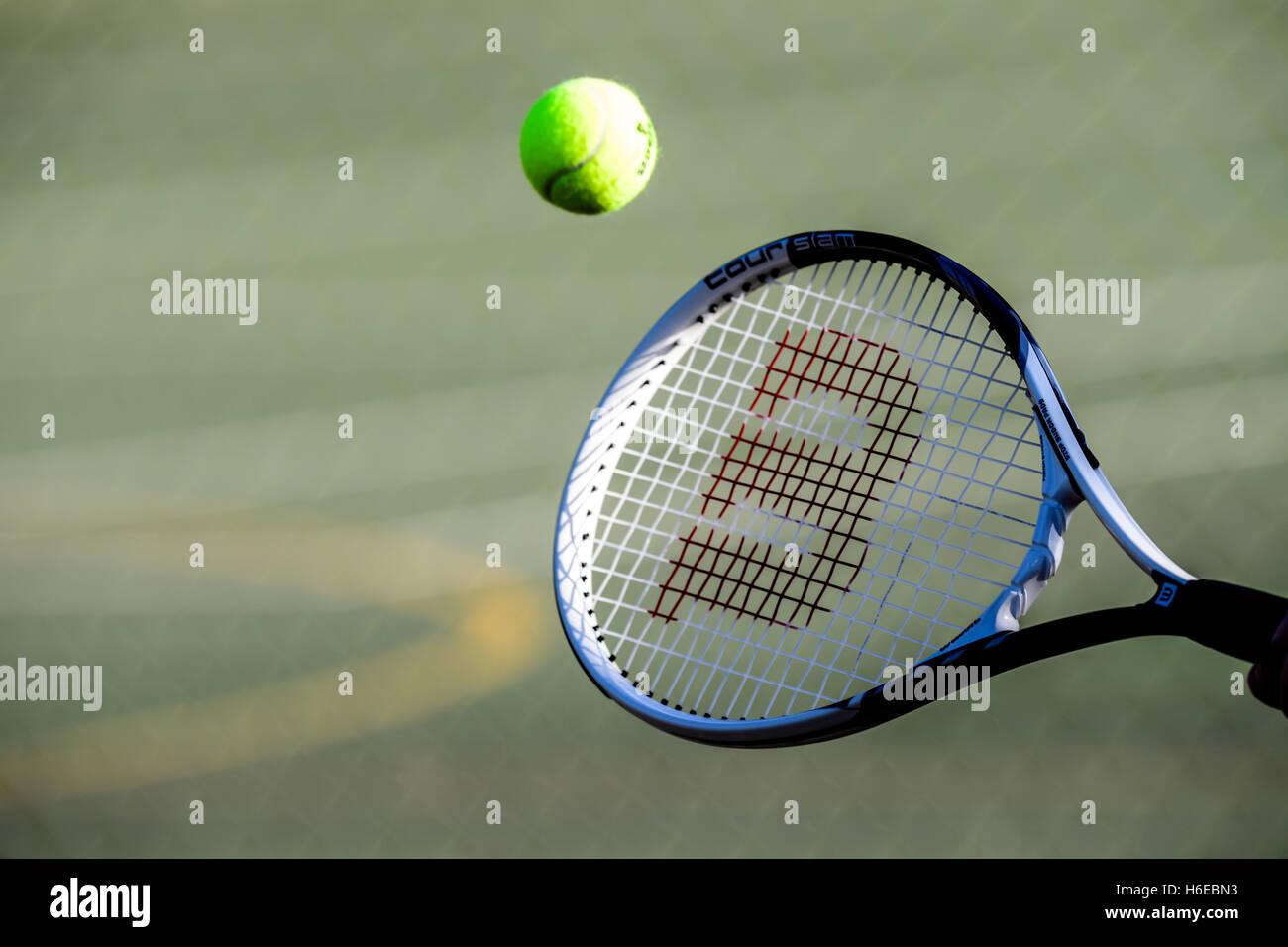 Tennisball schlagen einen Schläger Stockbild