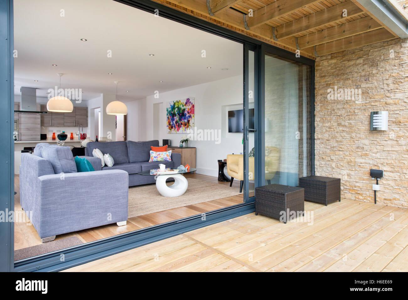 Ein offenes Wohnzimmer, Essbereich und Küche mit großen Schiebetüren ...