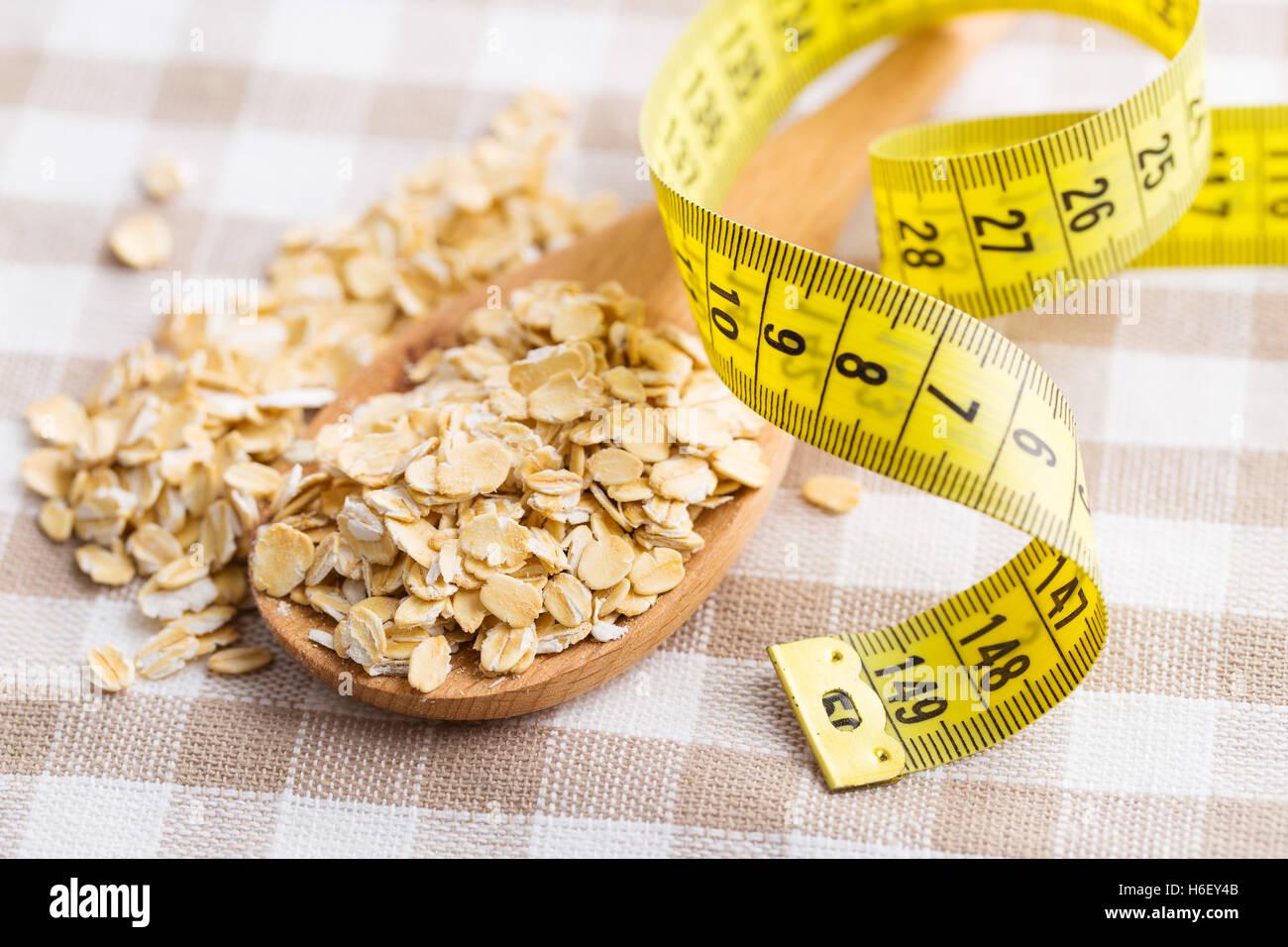 Das Diät-Konzept. Haferflocken und ein Maßband. Stockbild