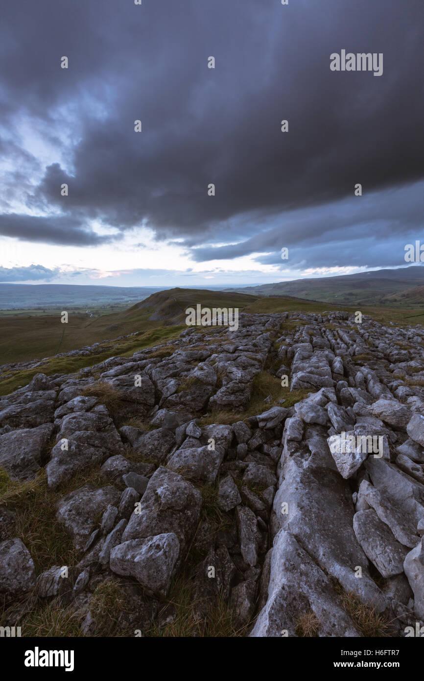 Kalkstein Pflaster auf Smearsett Narbe unter einem Gewitterhimmel, Yorkshire Dales National Park, England, UK Stockbild
