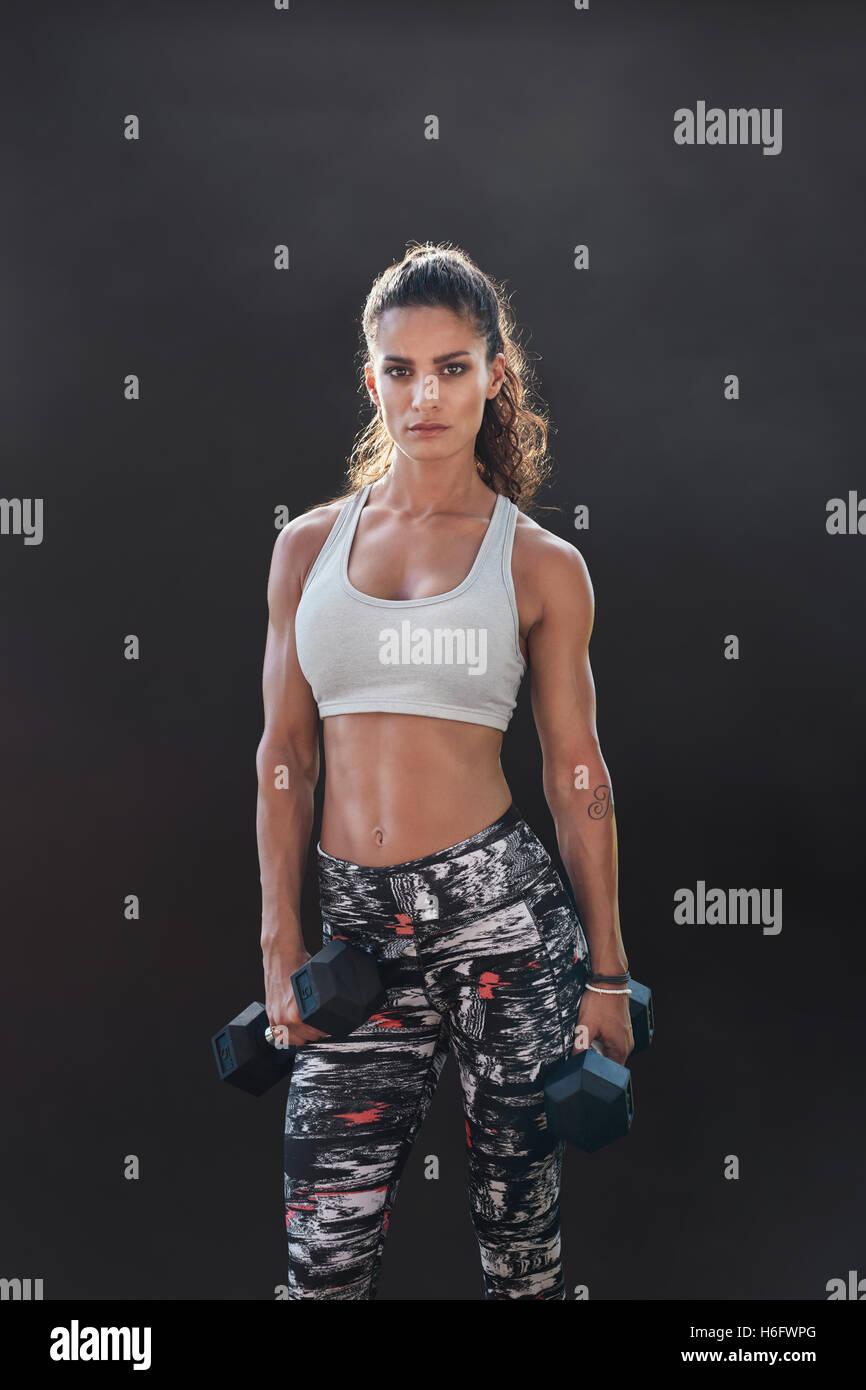 Fitness-Frau mit Hanteln trainieren. Schöne Fitnesstrainer auf schwarzem Hintergrund. Weibliches Modell mit Stockbild