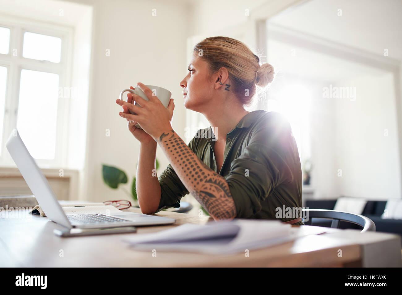 Innenaufnahme der jungen Frau mit Kaffee wegschauen und denken. Nachdenkliche Frau Büro zu Hause zu sitzen. Stockbild