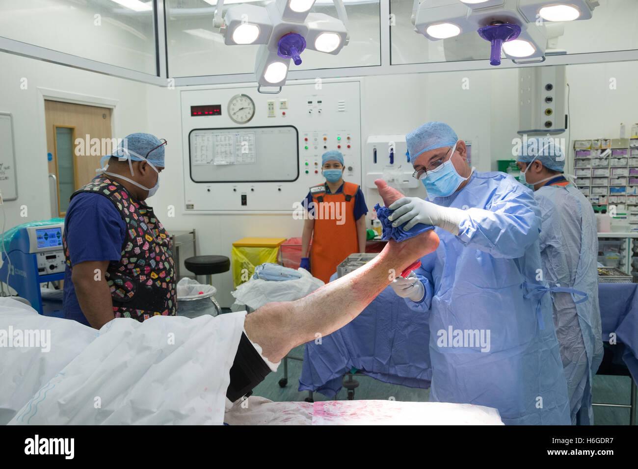 Ein Chirurg und Personal vorbereiten ein Patienten für eine Operation vor der Durchführung einer offenen Stockbild