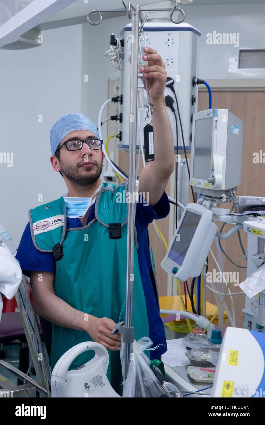 Ein Anästhesist prüft einen medizinischen Tropf während einer Operation in einem Krankenhaus-Theater Stockbild