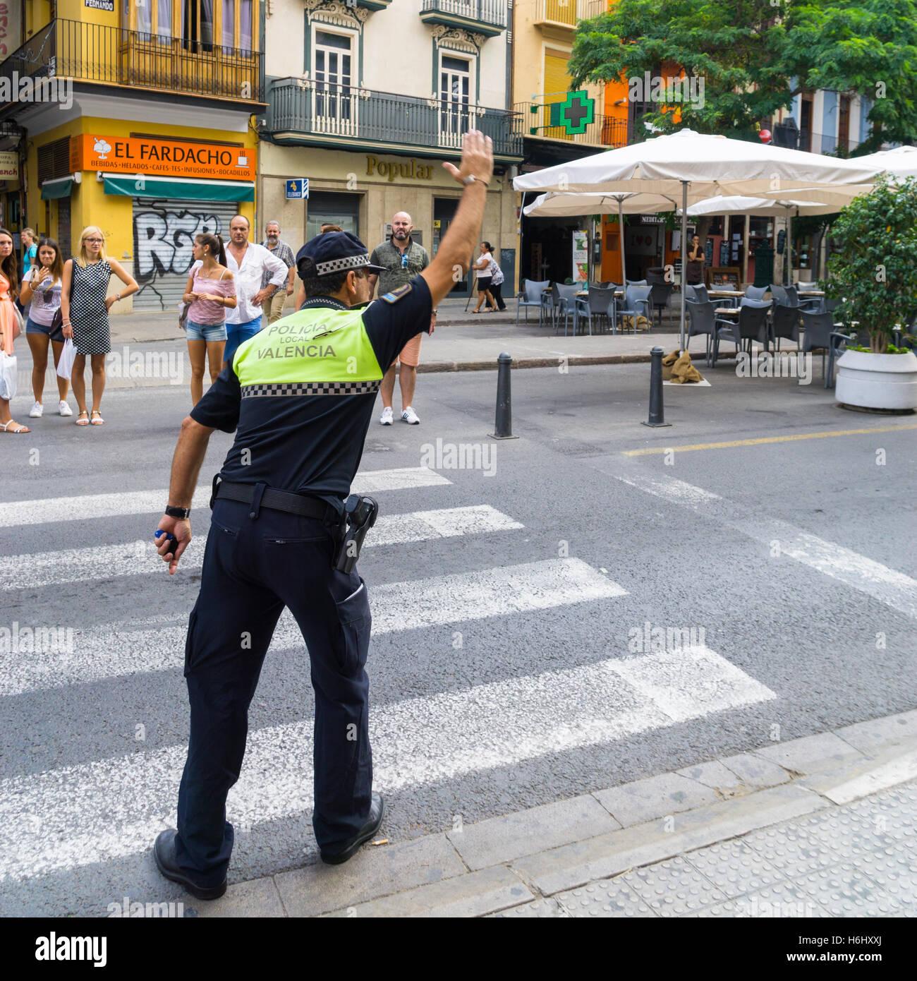 Ein spanischer Polizist regelt den Verkehr auf einen Fußgängerüberweg in Valencia, Spanien Stockbild
