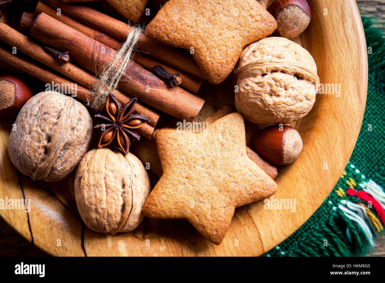 Rustikale Weihnachts-Dekoration mit Lebkuchen, Nüssen und weihnachtlichen Gewürzen über Holzplatte Stockbild