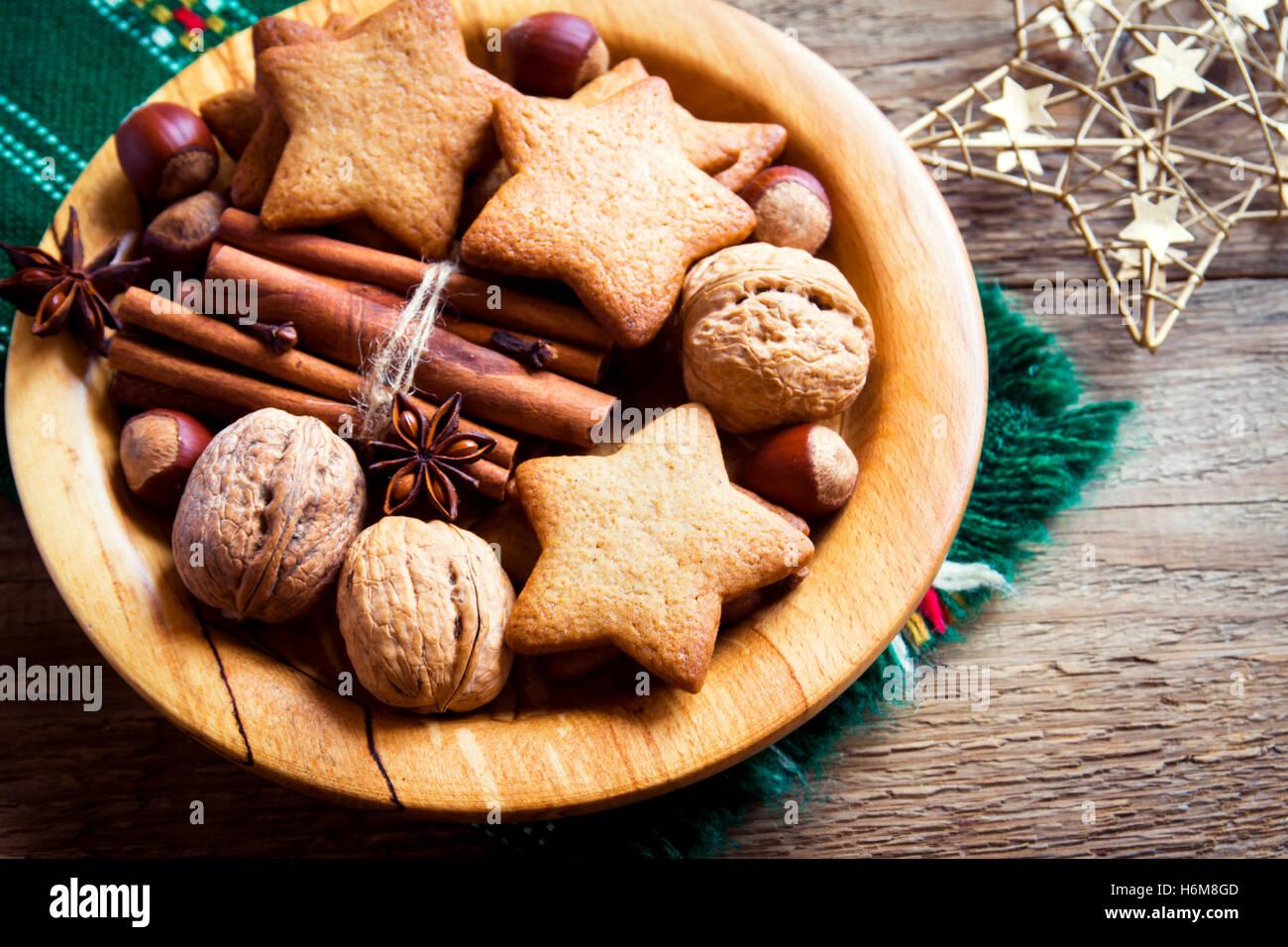 Rustikale Weihnachts-Dekoration mit Lebkuchen, Nüssen und weihnachtlichen Gewürzen über hölzerne Stockbild
