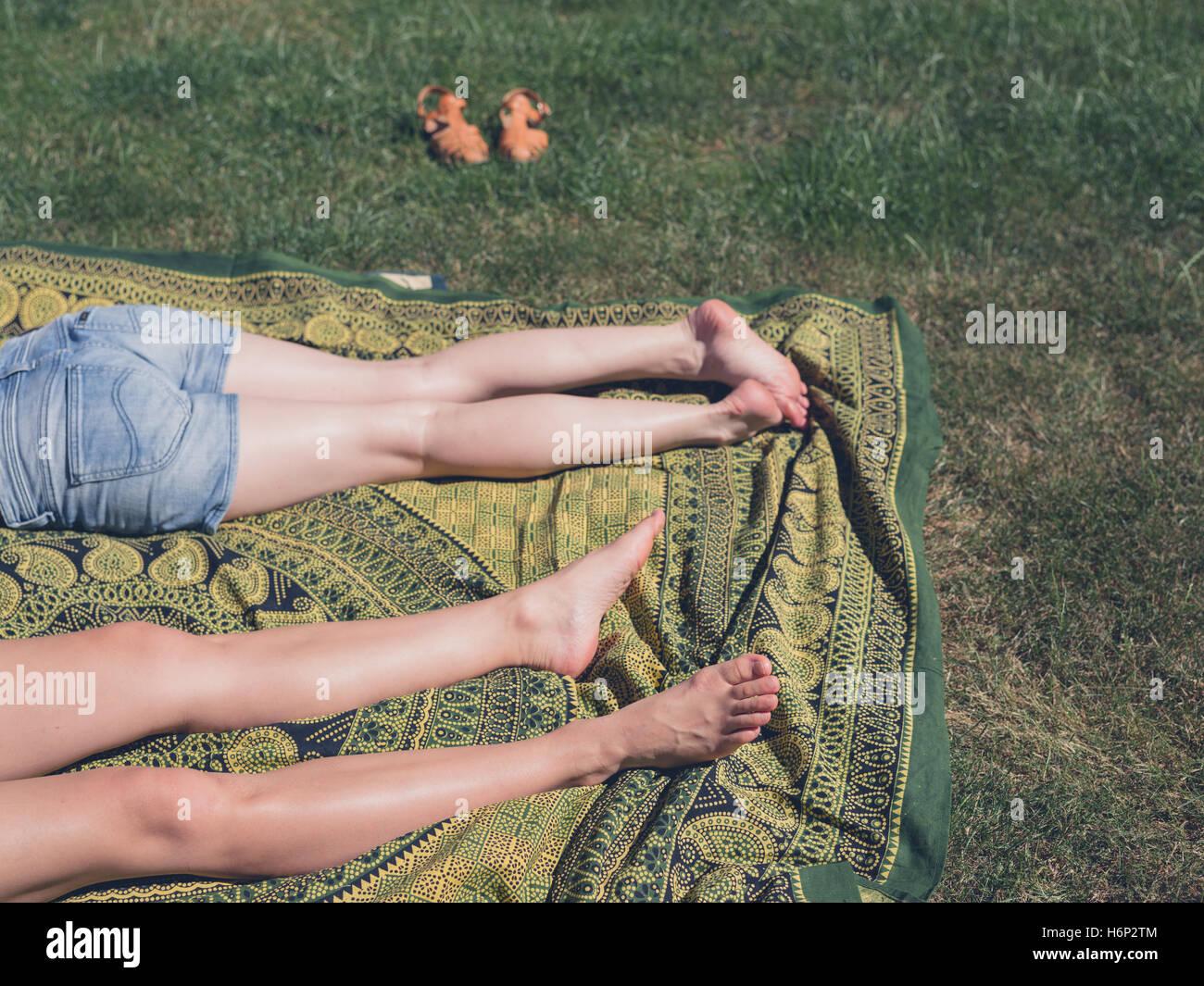 Die Beine der beiden jungen Frauen sind, entspannen Sie sich auf dem Rasen außerhalb an einem sonnigen Tag Stockbild