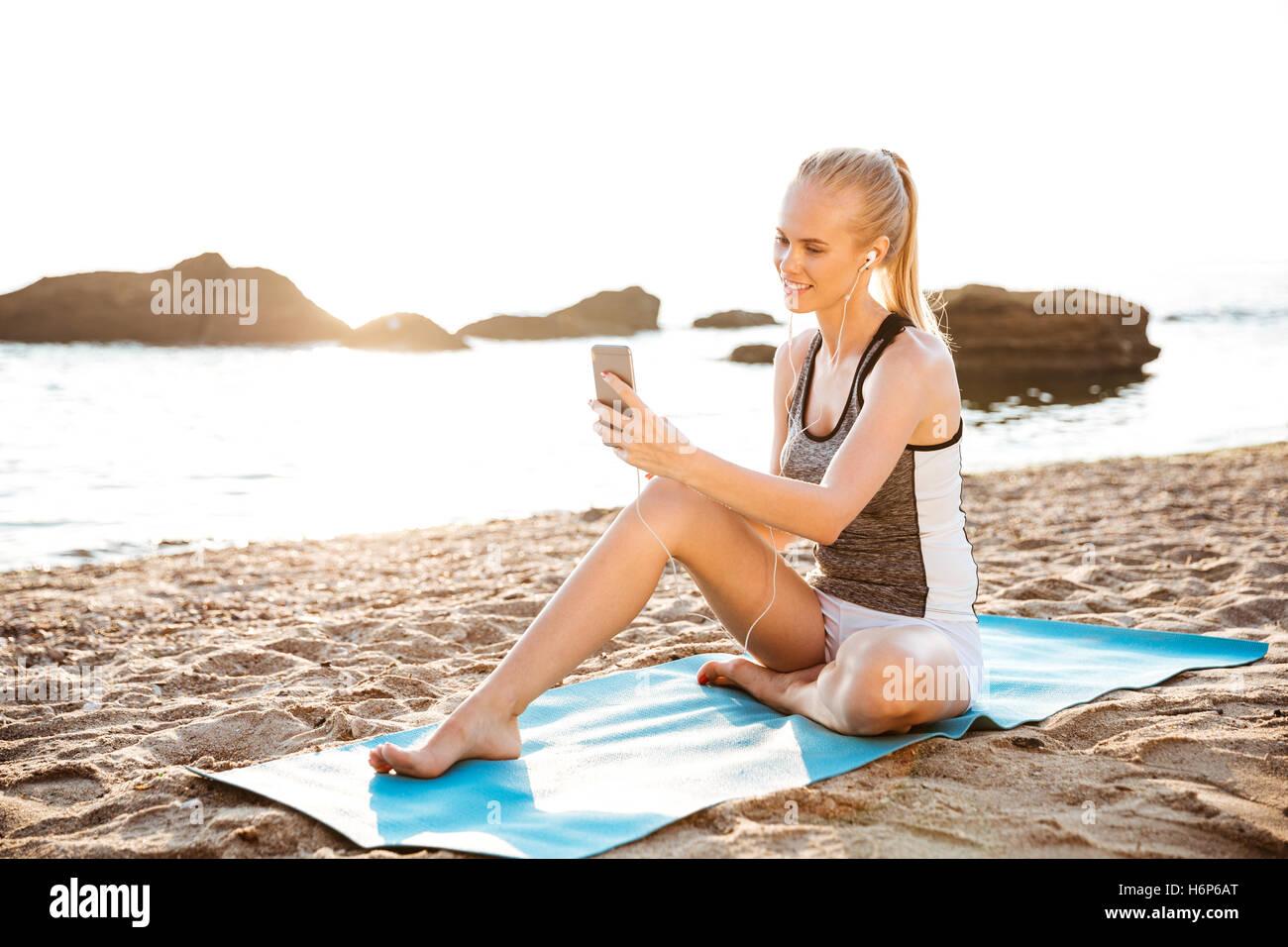 Attraktive junge Frau glücklich machen Yoga und mit Handy auf Matte im Freien am Strand sitzen Stockbild