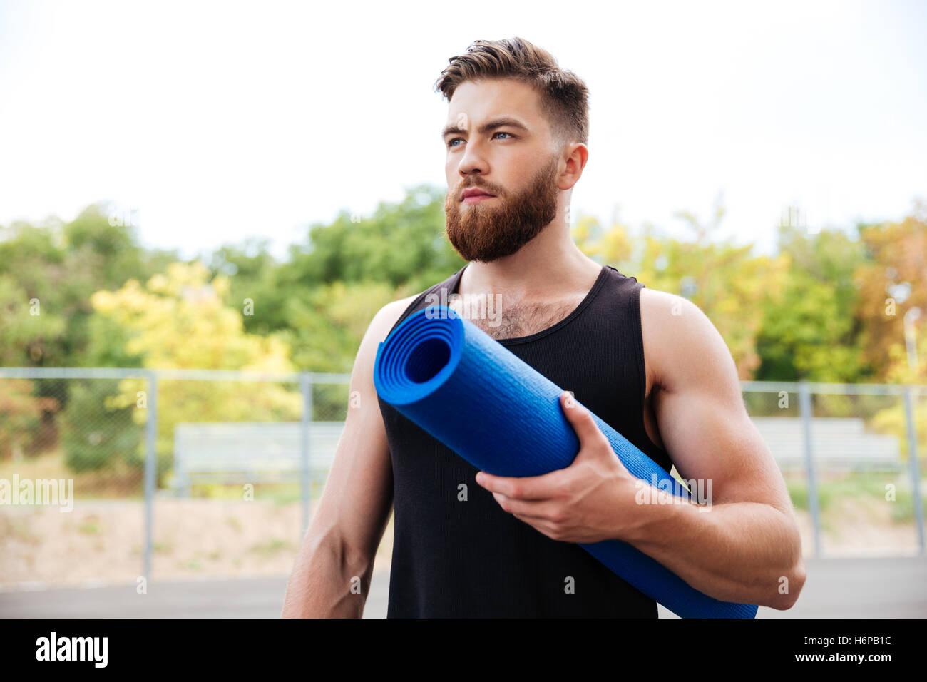 Konzentrierte schwere männliche Yogalehrerin Matte stehen im Freien halten Stockbild