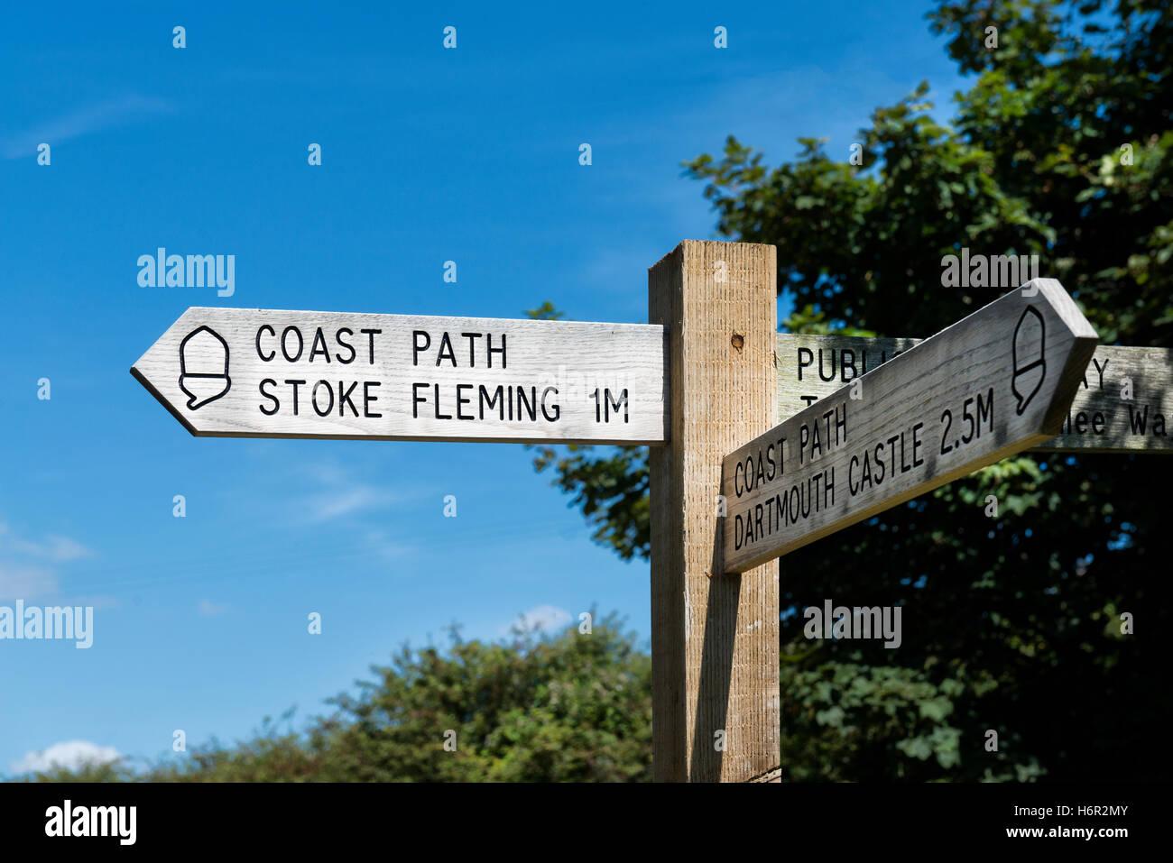 Landschaft Holz- finger Post zeigen Coast Path, stoke Fleming und Dartmouth Castle gegen Bäume und einem klaren Stockbild