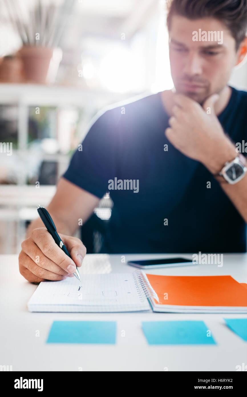 Geschäftsmann, schreiben Sie einige wichtige Hinweise im Tagebuch an seinem Schreibtisch bei der Arbeit. Männliche Stockbild