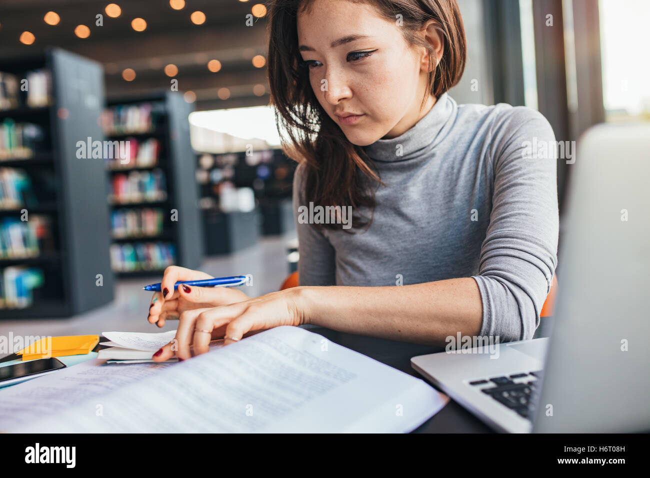 Junge Frau an einem Buch studieren und Abbau Hinweis beim Sitzen am Schreibtisch Bibliothek. Asiatische Studentin Stockbild