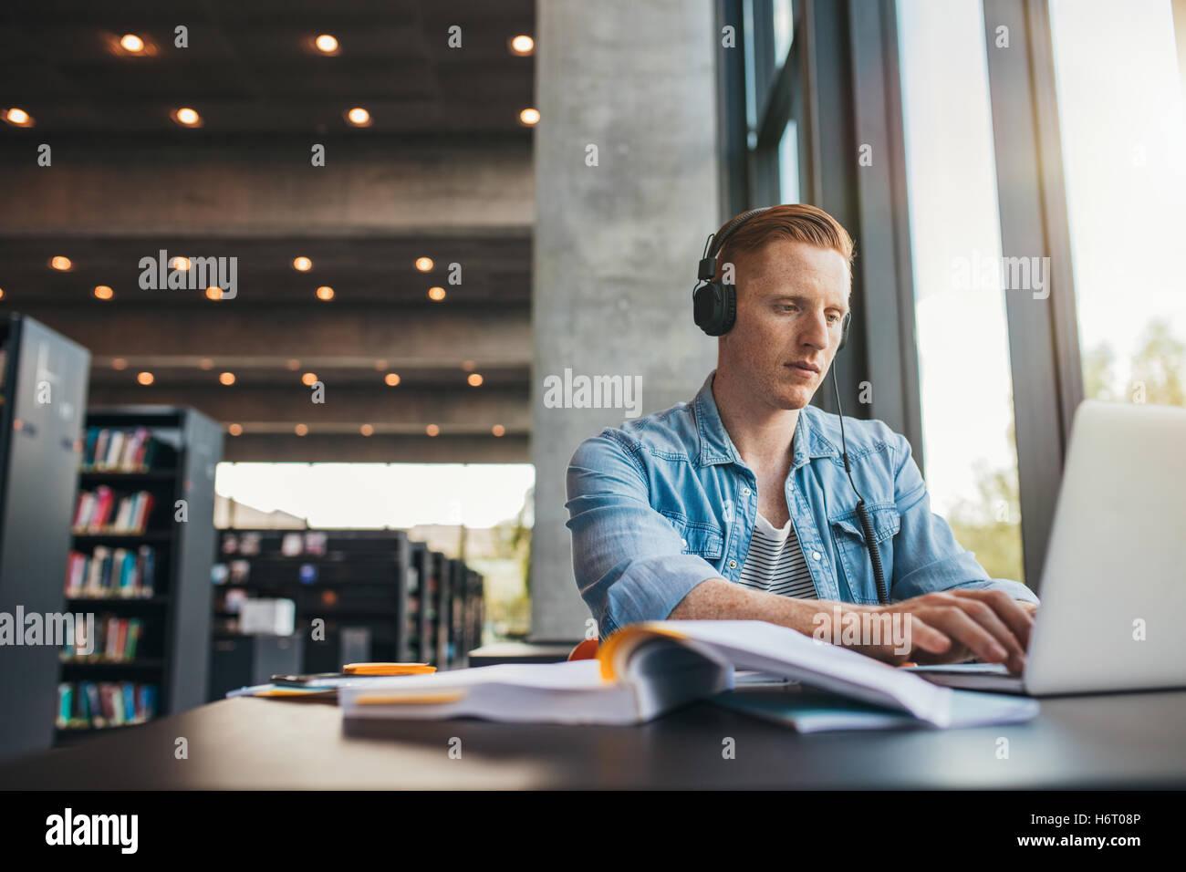 Junge männliche Schüler mit Kopfhörern auf dem Laptop zu studieren. Hübscher kaukasischen Mann Stockbild