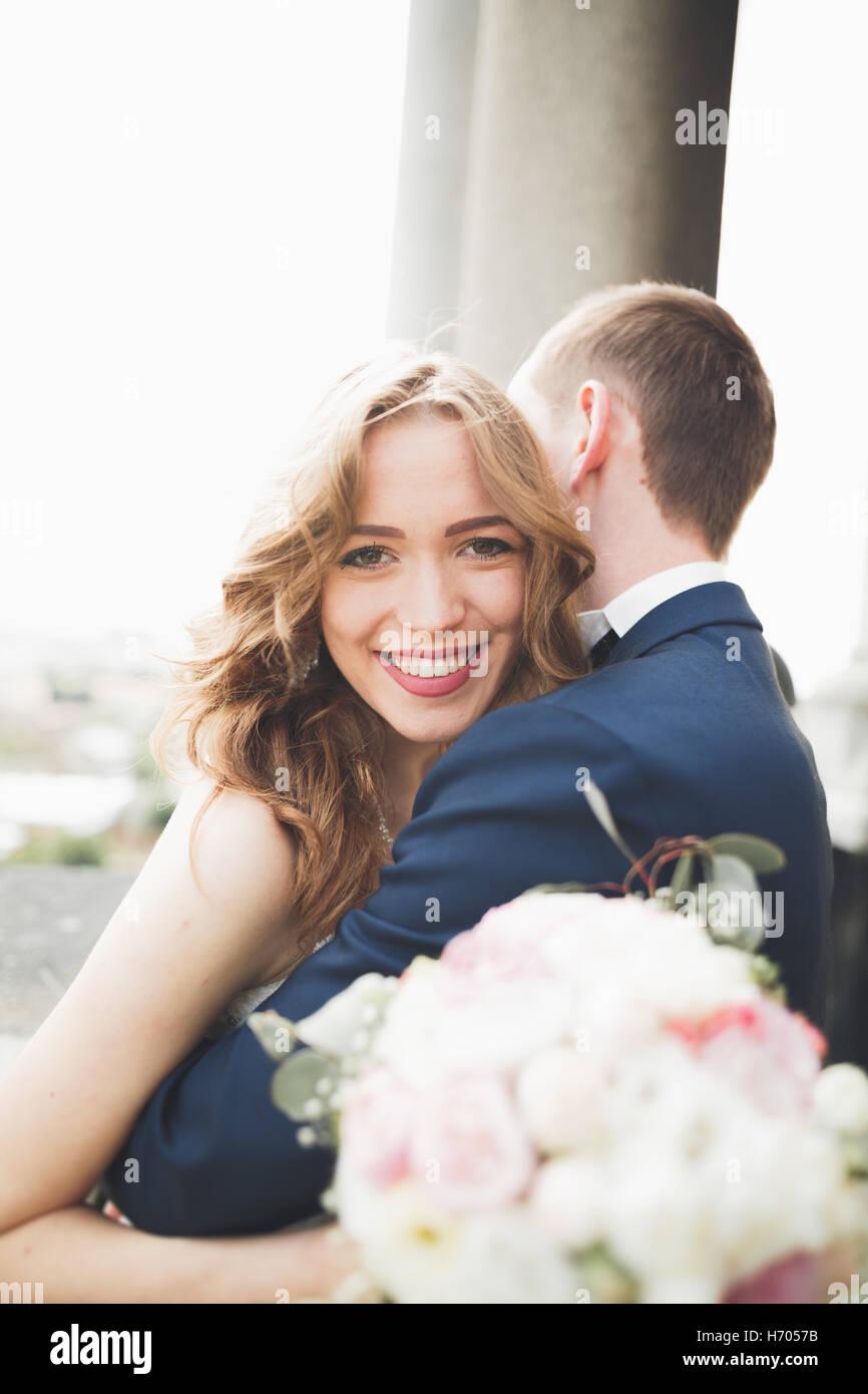 Schöne stilvolle Hochzeit paar küssen und umarmen auf Hintergrund Panoramablick auf die Altstadt Stockbild