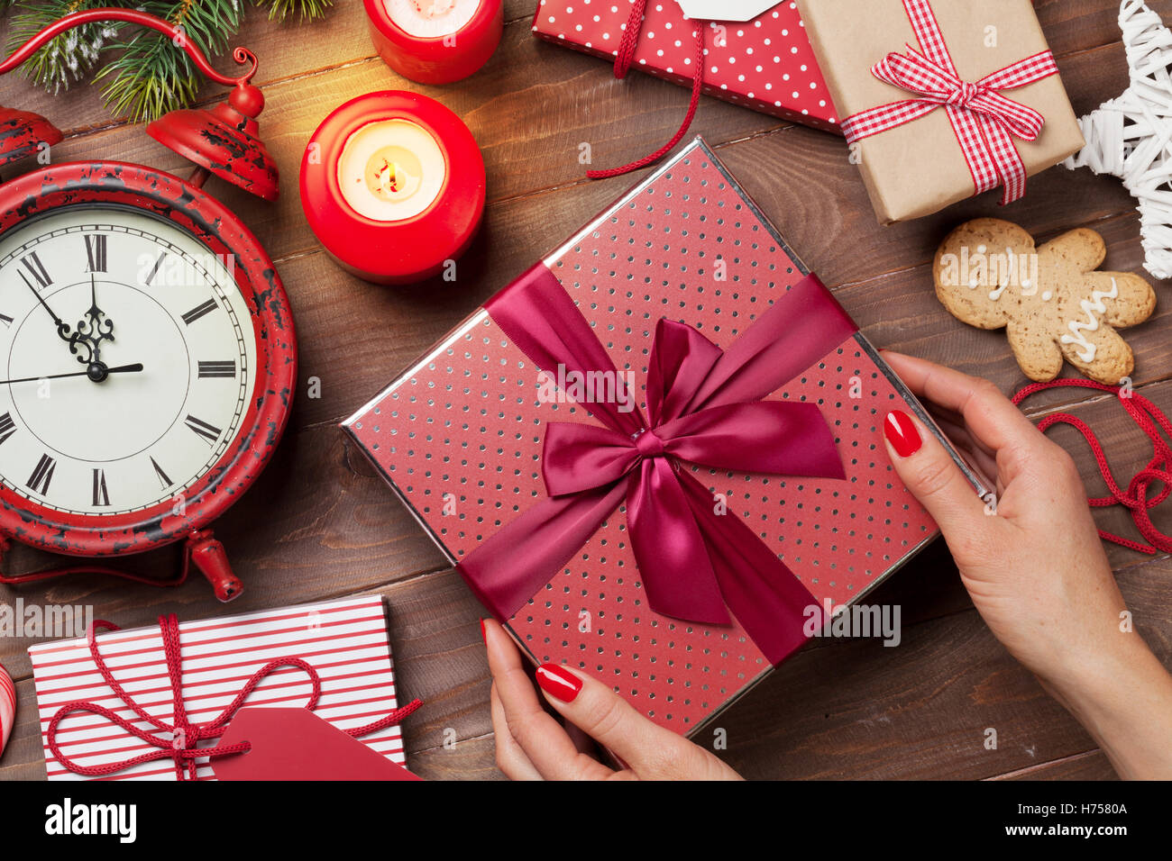 Weibliche Hände halten Weihnachtsgeschenk über Holztisch. Ansicht ...