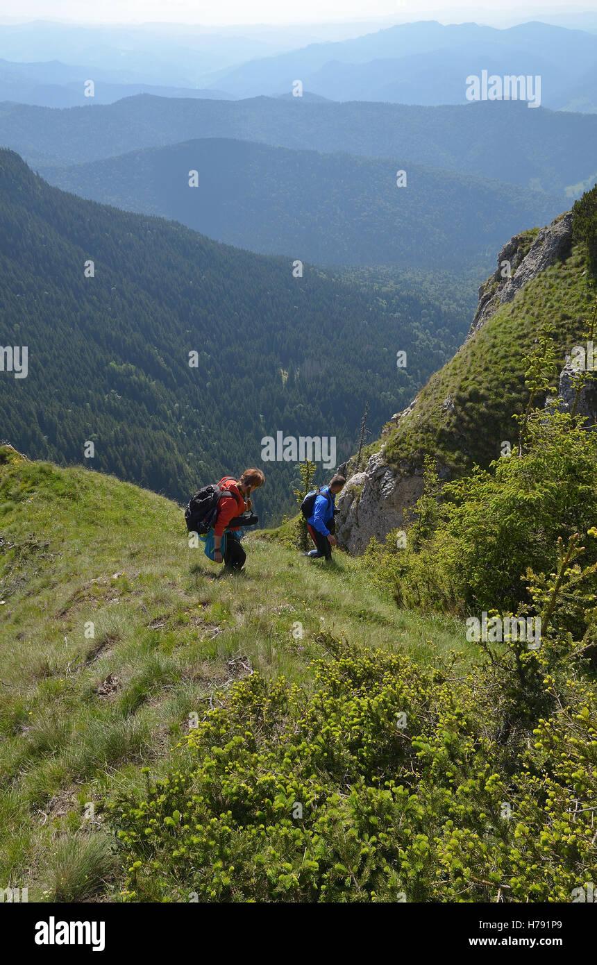 Paar absteigend einen Berggipfel mit einer Landschaft im Hintergrund der FSME Stockbild