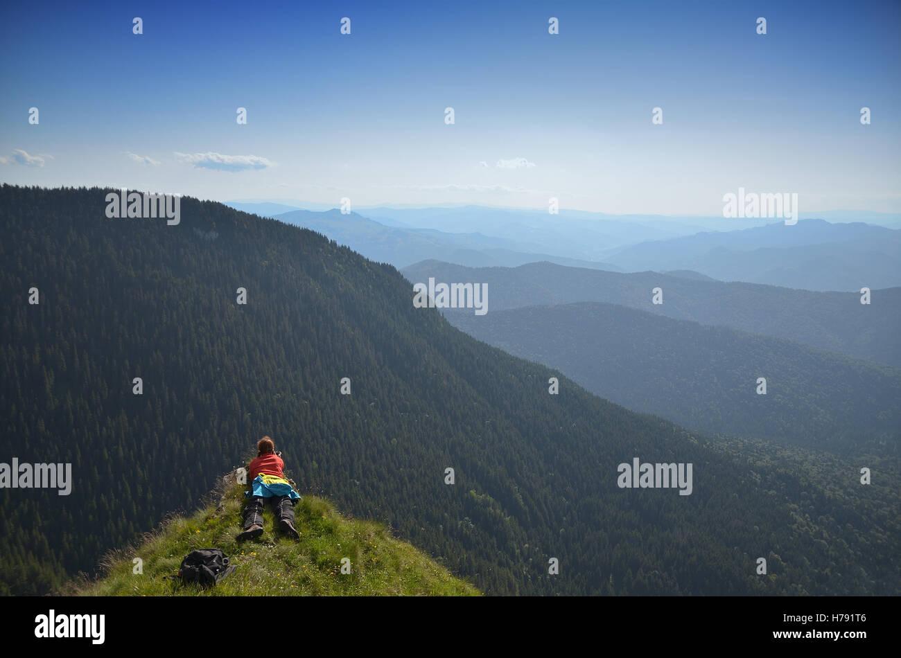 Weibliche Fotografen auf einem Berggipfel, schießen die Landschaft Stockbild