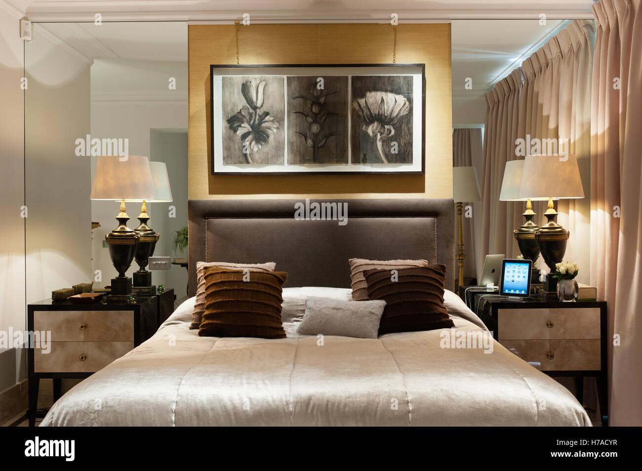 Botanische Illustrationen über Doppelbett mit passenden Nachttischlampen und vertiefte verspiegelten Wänden Stockbild