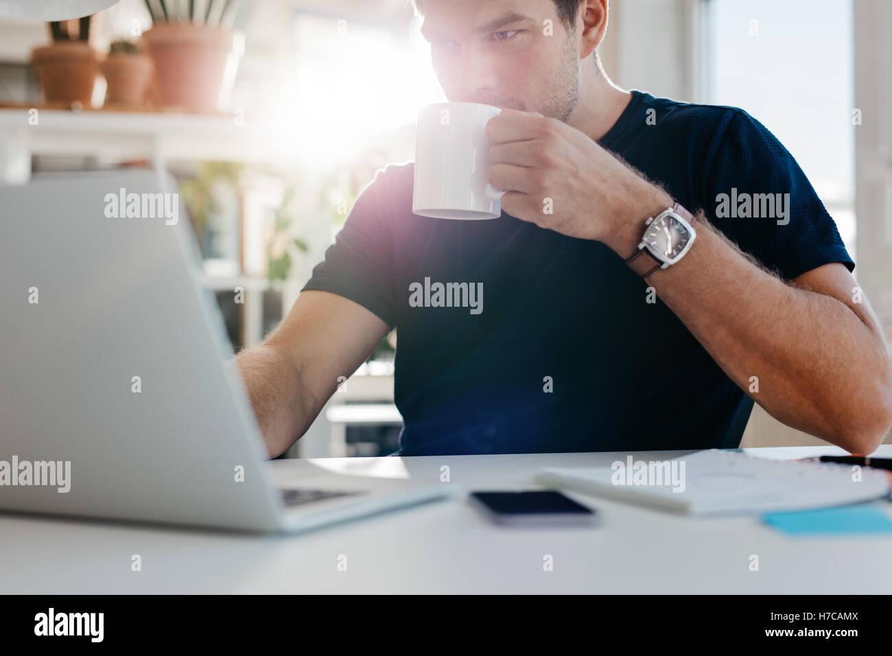 Bild der junge Geschäftsmann mit Tasse Kaffee mit Blick auf Laptop-Bildschirm am Arbeitsplatz. Männliche Stockbild