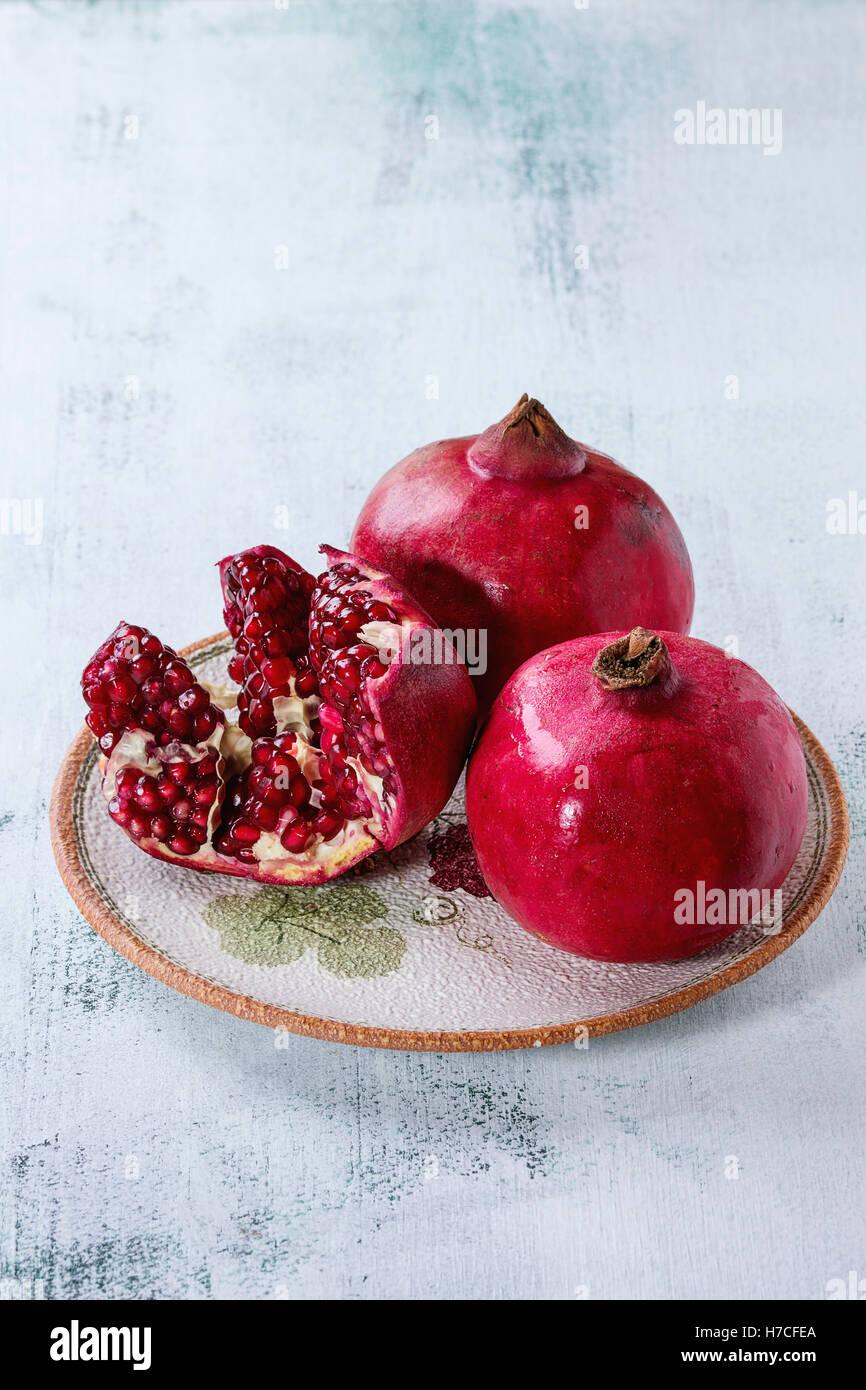 Reife Slice und ganze Granatäpfel auf verzierte Keramikplatte über weißen hölzernen Hintergrund. Stockbild