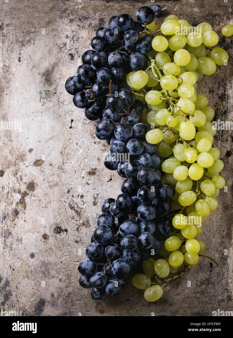Die Trauben reifen nassen roten und weißen Trauben über alte Textur Metall Hintergrund. Draufsicht mit Stockbild