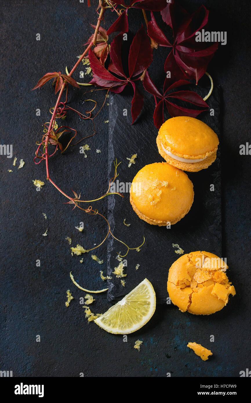 Ganze und gebrochene orange Zitrone hausgemachte Makronen mit weißer Schokolade, Zitronenscheibe und Lebensfreude, Stockbild