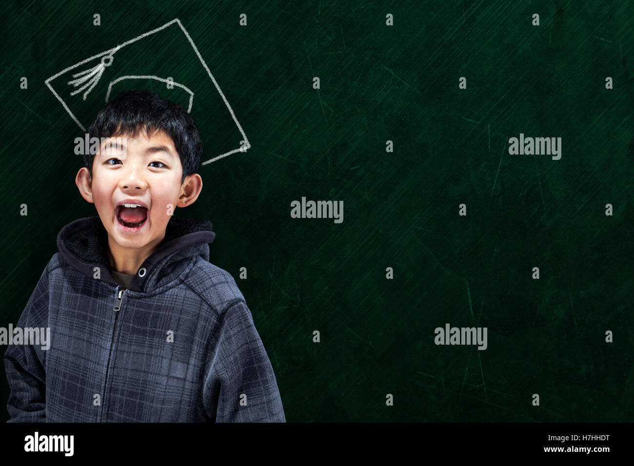 Jubilent Asian Boy In Klassenzimmer Mit Diplom Hut Auf Tafel Hintergrund Und Kopie Raum Konzept