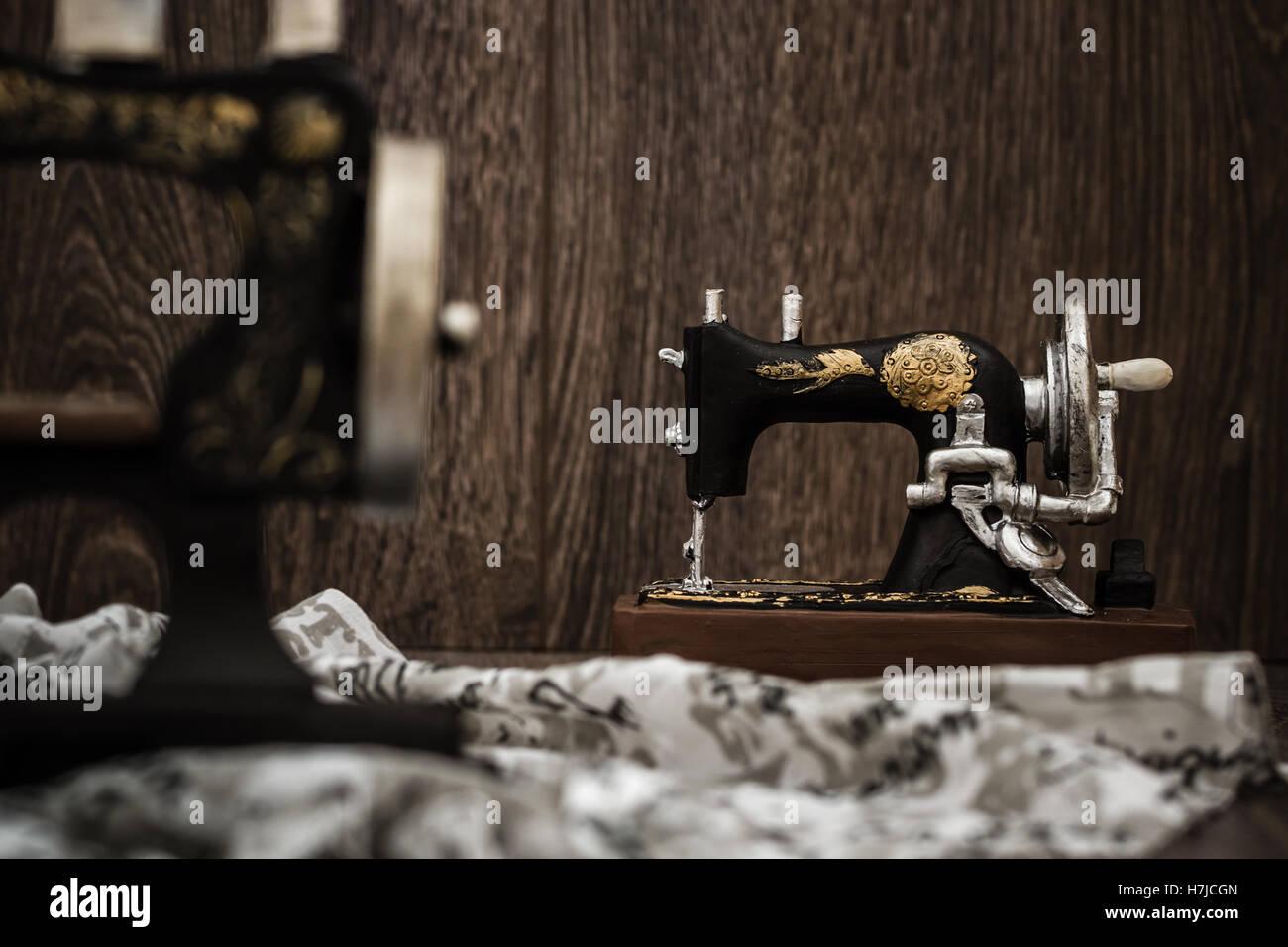 Kleinen nostalgischen dekorative Nähmaschine auf braunem Holz Hintergrund Stockbild