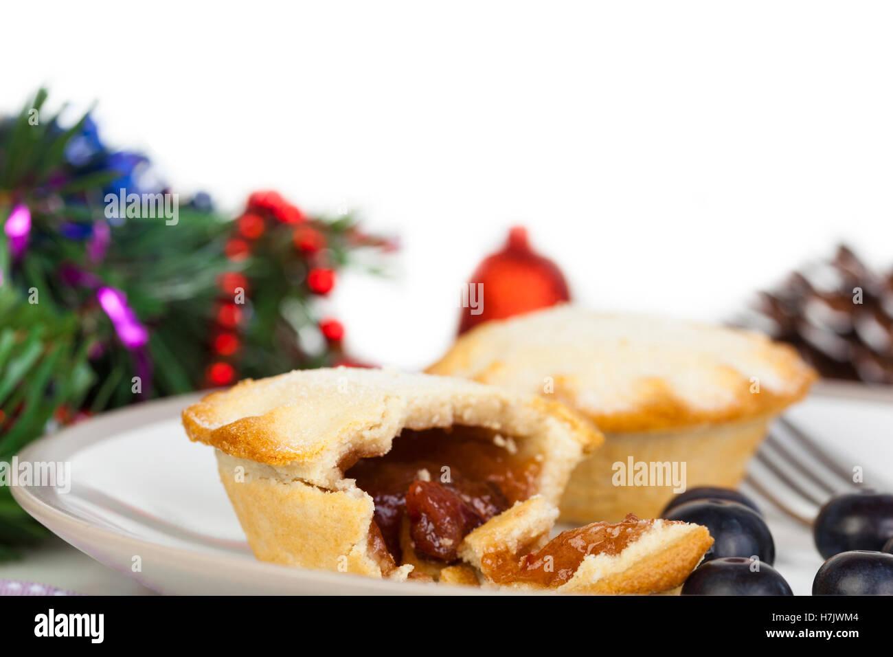Teil gegessen Mince Pie mit Heidelbeeren und Weihnachts-Dekorationen auf weißem Hintergrund Stockbild