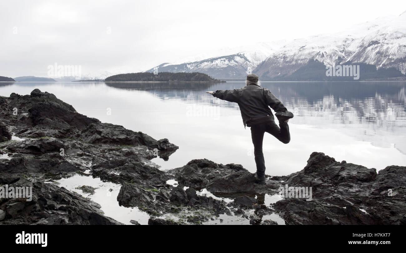 Mann tut eine dumme Yoga stellen an einem steinigen Strand in Southeast Alaska mit gedämpften Farbtöne Stockbild