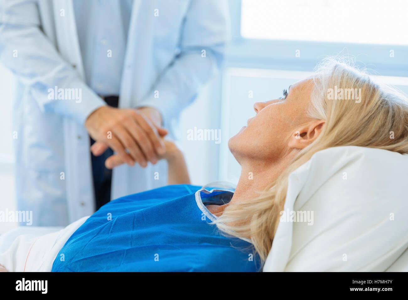 Arzt des Patienten halten Hand in Krankenzimmer Stockbild