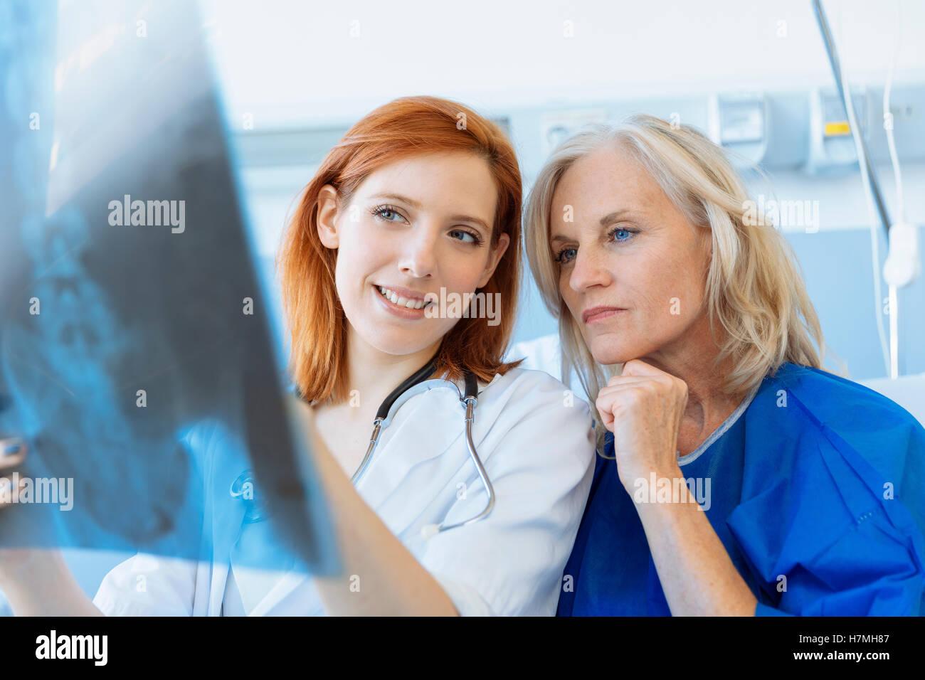 Arzt zeigt Xray zu einem älteren Patienten im Krankenhaus Stockbild