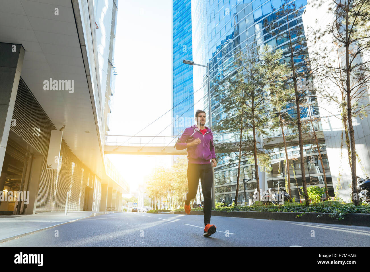 Athlet mit Kopfhörern laufen in der Stadt Stockfoto
