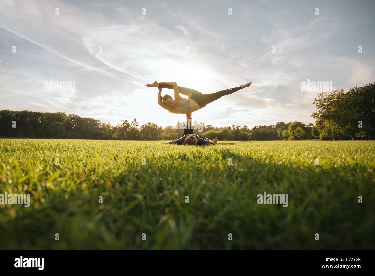 Passen Sie junges Paar beim Acro Yoga. Mann auf dem Rasen liegen und Frau in seinen Füßen balancieren. Stockbild