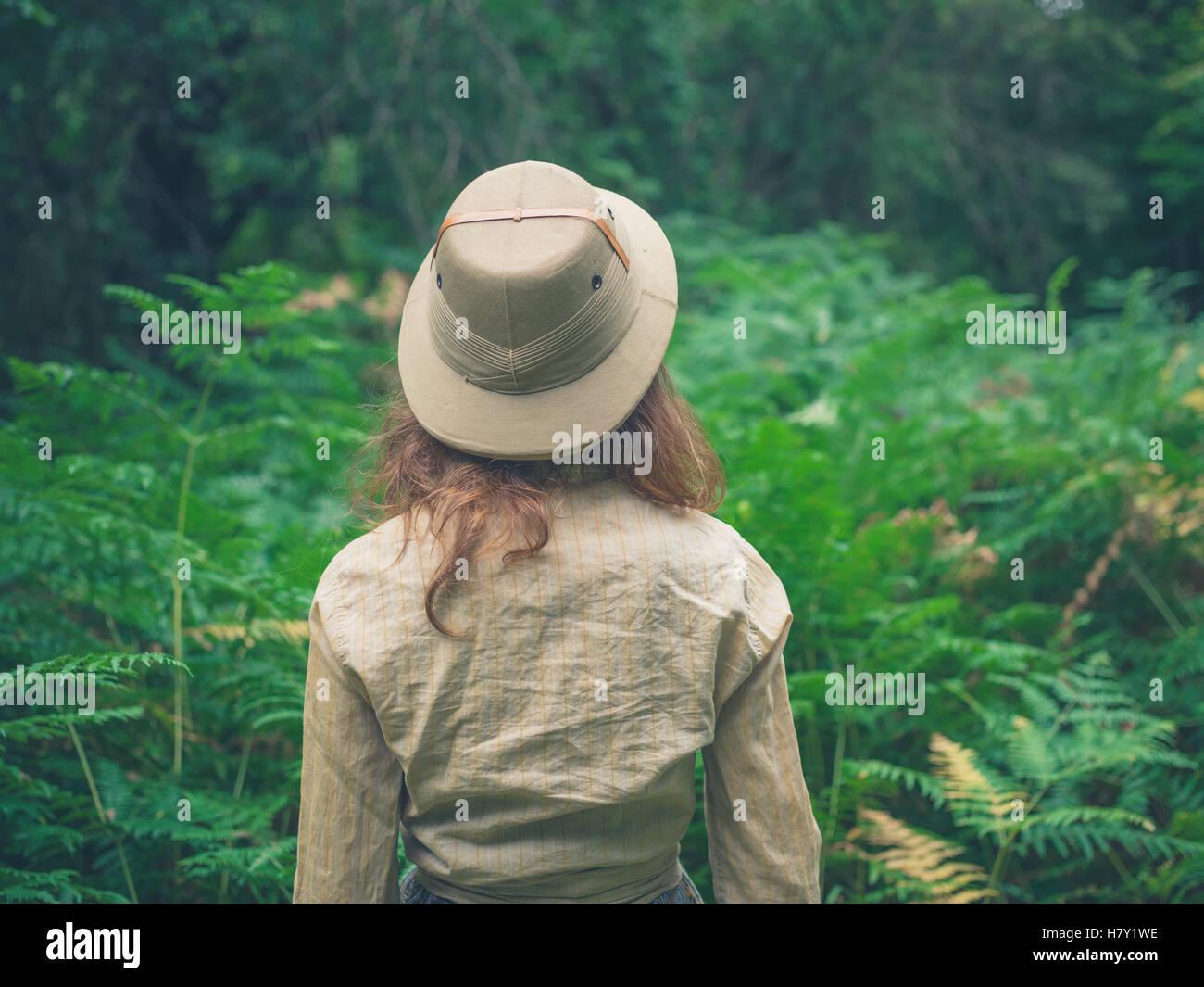 Eine junge Frau mit einem Safari-Hut ist einen Wald mit vielen grünen Farnen erkunden Stockbild