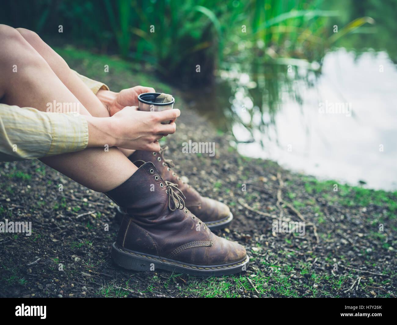 Eine junge Frau sitzt an einem Teich im Wald und ist mit einer Tasse Tee Stockbild