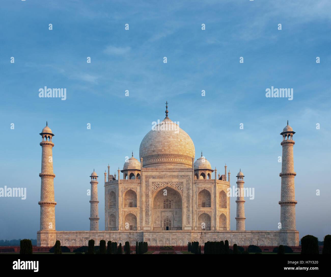 Ein schöner Morgen orange Leuchten am vorderen Marmorfassade der Tadsch Mahal mittig unter einer ruhigen blauen Stockbild