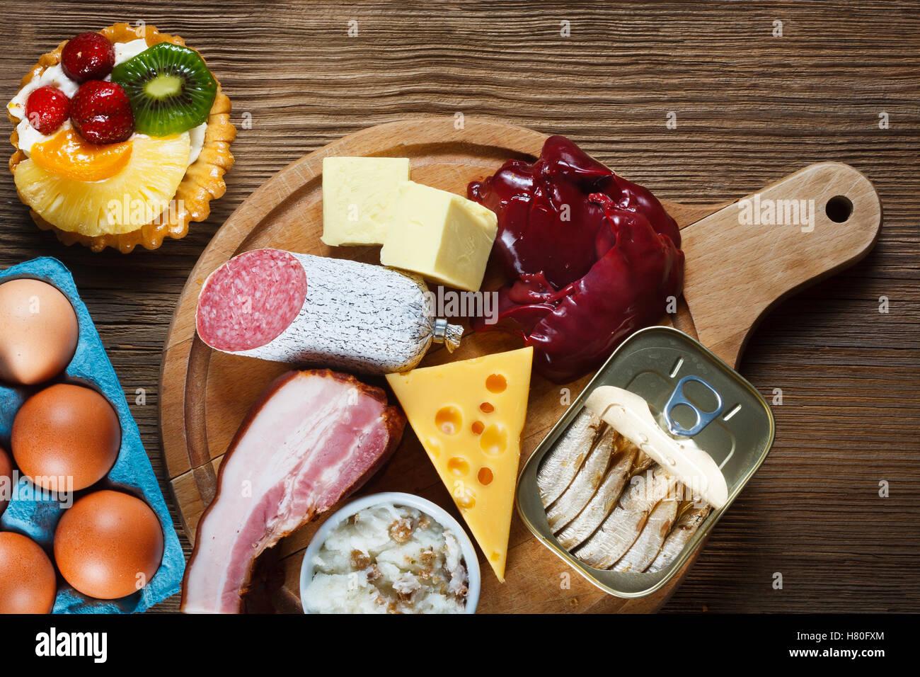 Lebensmittel reich an Cholesterin wie Eiern, Leber, gelben Käse, Butter, Speck, Schmalz mit Zwiebeln, Sardinen Stockbild