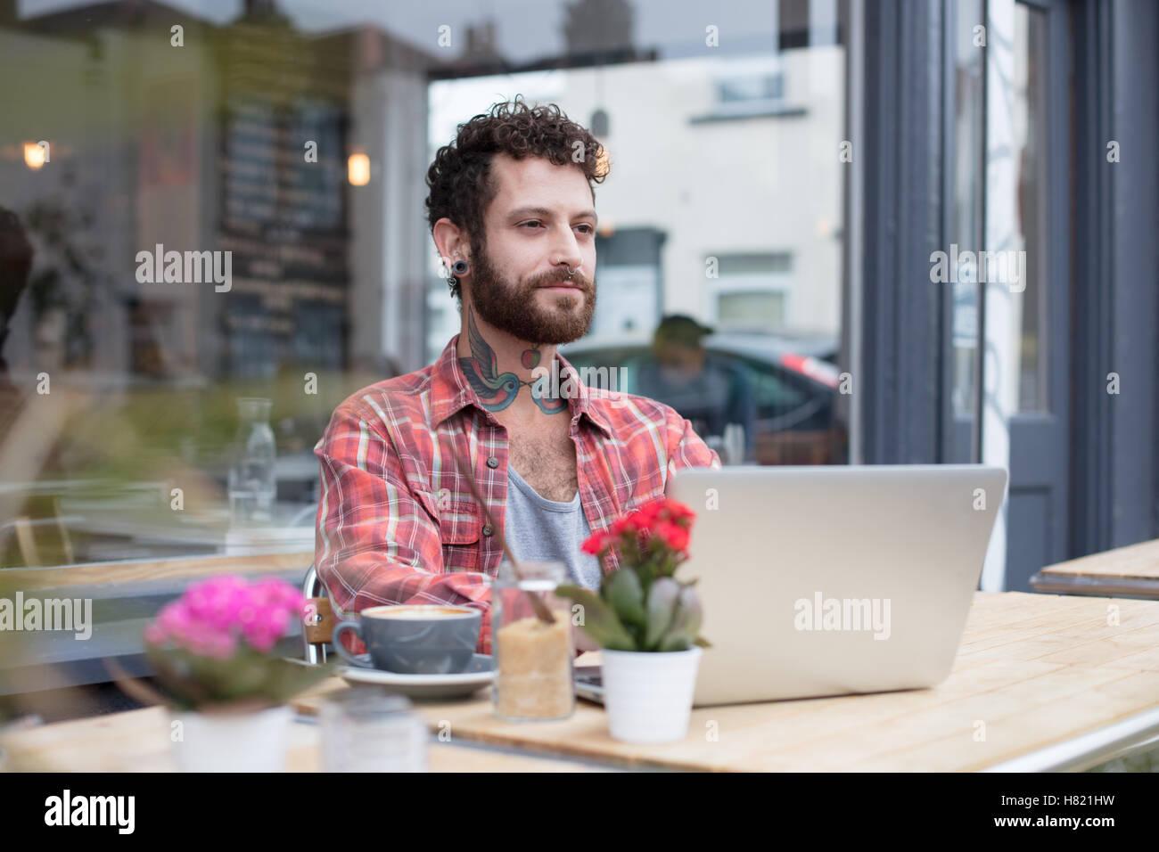 Junge tätowierte Hipster mit Laptop vor café Stockbild