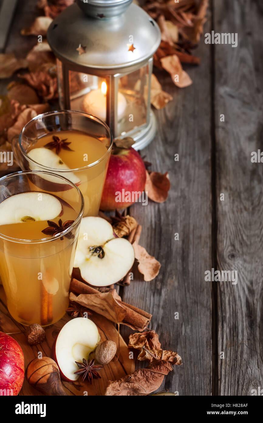 Heißer Apfelwein mit Zimtstangen und Gewürzen auf Herbst Blätter Hintergrund Stockfoto
