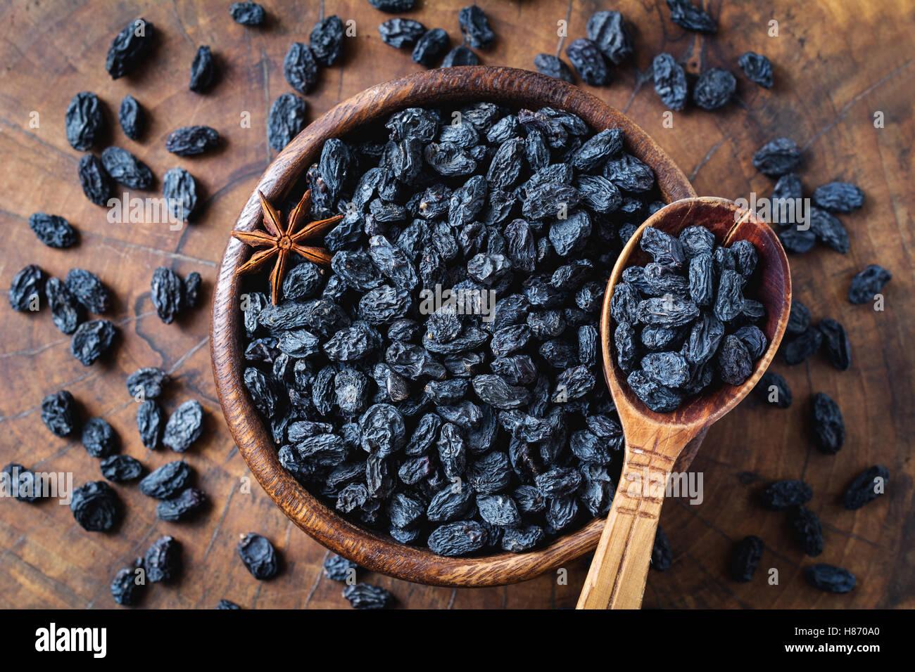 Schwarze Rosinen in Holzschale, Ansicht von oben. Gesunder Snack, diätetisches Lebensmittel für gutes Stockbild