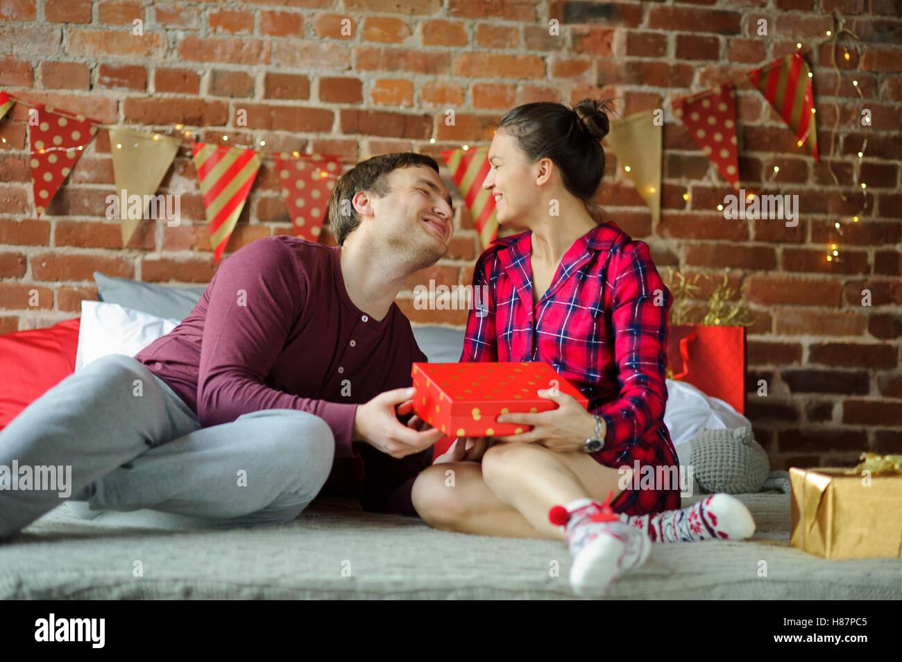Weihnachten. Junges Paar gratulieren einander einen sanften Kuss ...