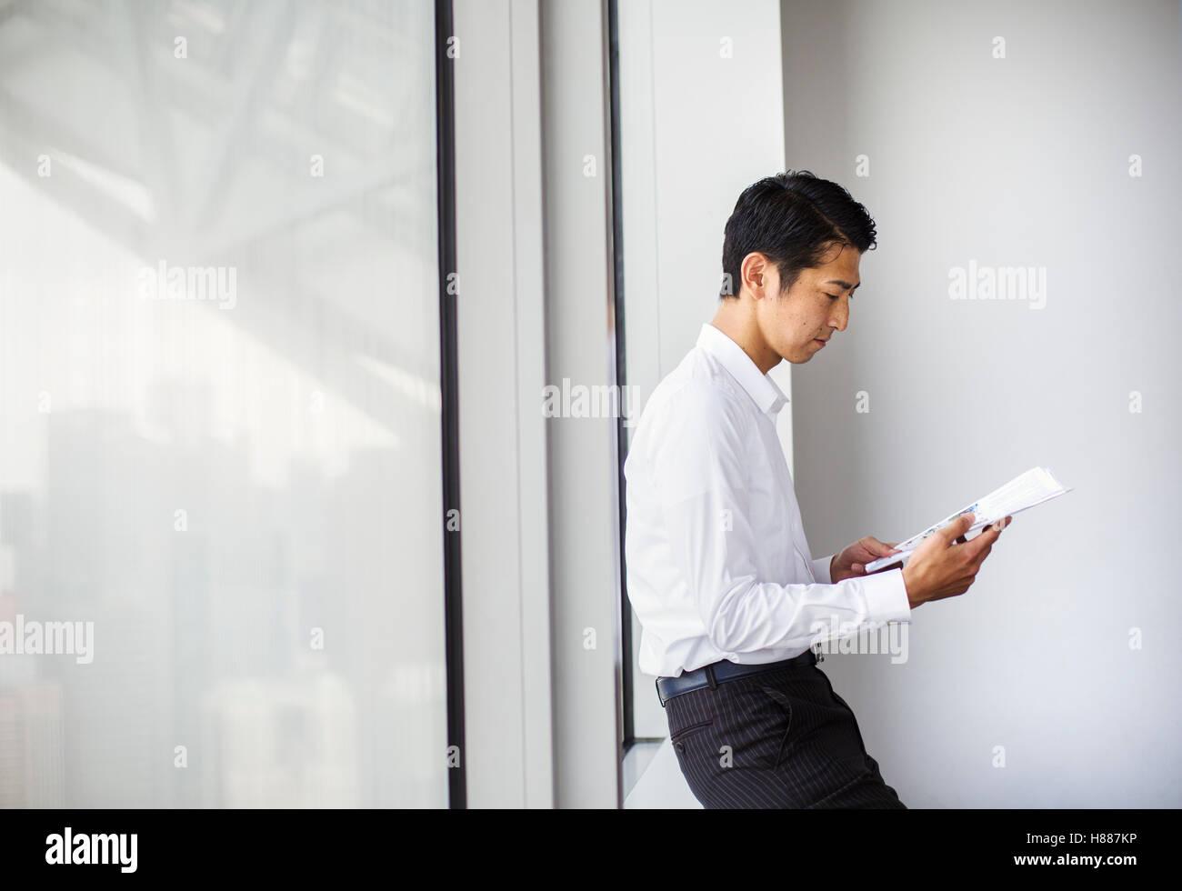 Ein Geschäftsmann im Büro durch ein großes Fenster lesen Papierkram. der Fensterbank gelehnt. Stadtbüro. Arbeitsleben Stockfoto