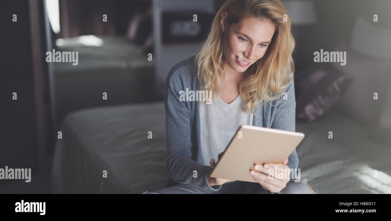 Schöne blonde Frau mit Tablet zu Hause Stockbild
