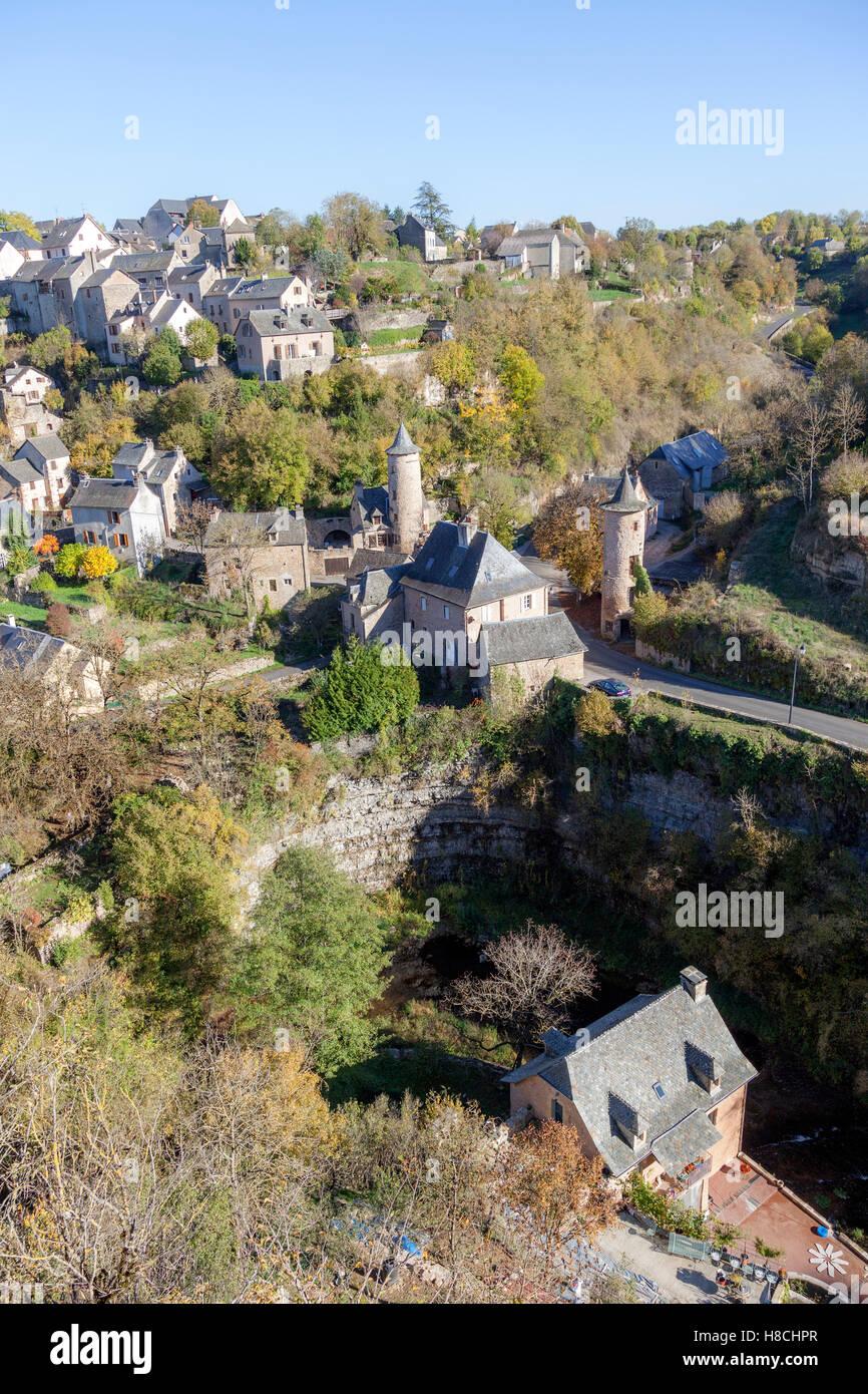 Das Bozouls Loch im Herbst und das untere Dorf mit seinen zwei mittelalterliche Wachtürme (Frankreich). Das Stockbild