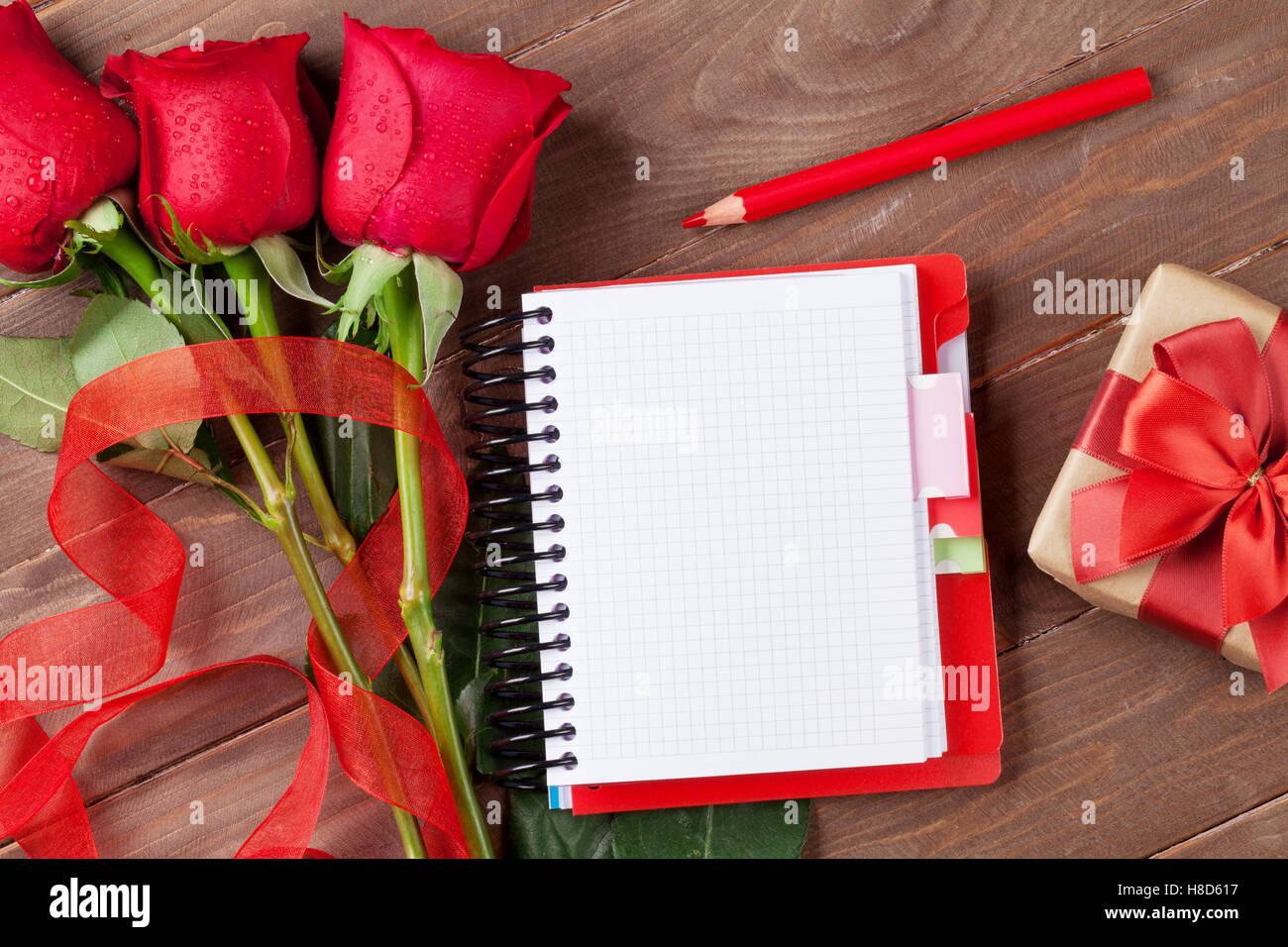 Liebe Brief Notizblock, rote Rosen und Geschenk-Box auf Holztisch ...