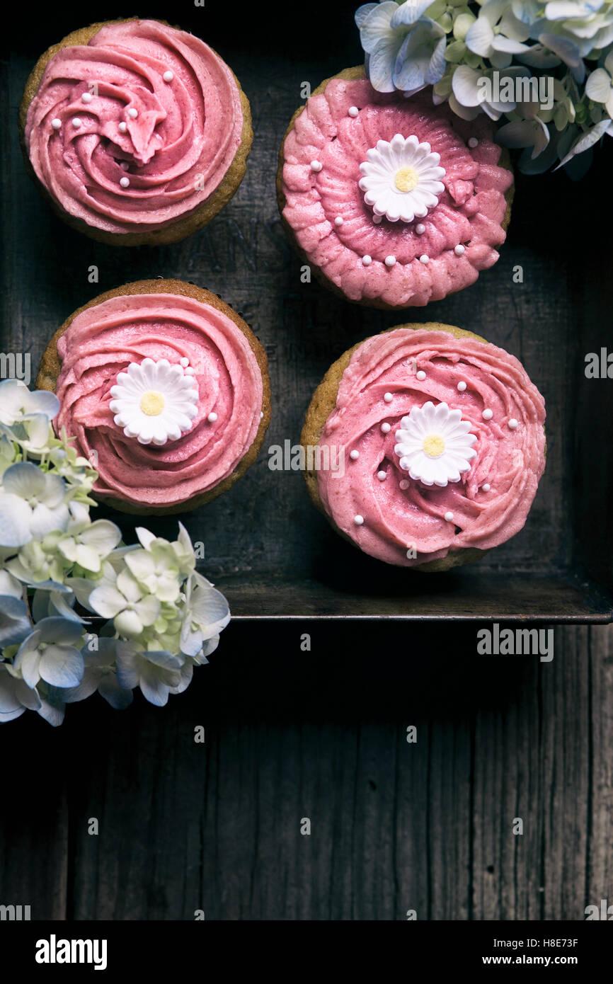 Rosa Geeiste Muffins auf einem Vintage Brett mit Blumen Stockfoto